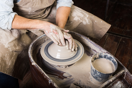 fireclay: pottery, workshop, ceramics art concept - closeup on working potters wheel with raw clay and man hands, a male sculpt a utensil with fingers, master in apron, top view
