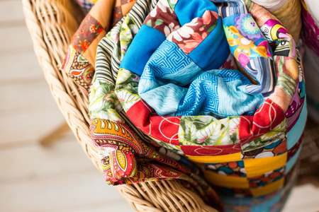 patchwork, quilting and fashion concept - macro on colorful quilt rolled into a tube and laid in a wicker chair, warehousing of finished product on a white background, top view