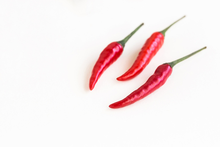pungent: red hot chili peppers, popular spices concept - three delicious juicy pod of red hot peppers lay on white background close up, top view, flat lay, empty space for the text