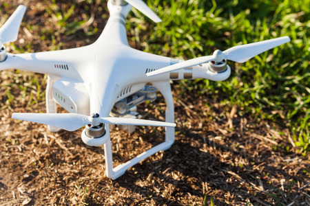 quadcopter summer outdoors, aerial imagery and hobby, recreation concept - quadrocopter landed on earth with grass, white superb drone fuselage with four propellers and high quality digital camera Stock Photo