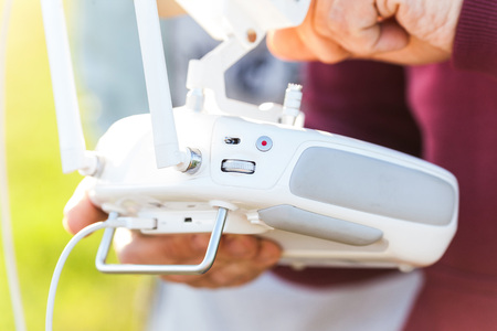 remote controls: quadcopter flight outdoors, aerial imagery and tech hobby, recreation concept - closeup on white remote radio control in pilot hands, modern high-tech solution for video filming and joy flying