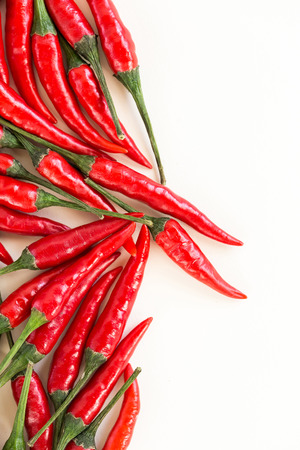 red hot chili peppers, popular spices concept - beautiful bunch of red chili hot pepper, fresh ripe pods with green peduncle on white background, flat lay, toop view, free space for text, vertical Imagens - 79962000