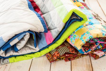 patchwork en mode concept - close-up op mooie kleurrijke dekbedden gevouwen op een witgekalkte houten vloer, close-up op patchwork producten op een witte achtergrond, bovenaanzicht, verticaal Stockfoto