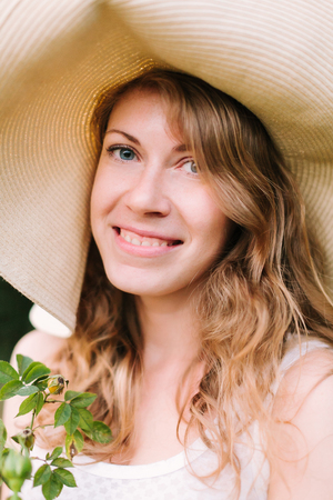 spring, summer, holidays, nature, beauty, decoration, gardening concept - close-up of beautiful blue-eyed woman in straw hat with flowing hair and friendly smile holding few twigs