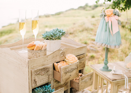 wedding decor outdoor. vintage beige dresser with small boxes decorated by sweets and fresh flowers. two glasses with champagne. nature recreation, date, engagement, romantic, event concept.