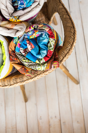patchwork and fashion concept - close-up on three colorful quilts rolled into a tube and laid in a wicker chair, warehousing of finished products on a white background, top view, vertical Stock Photo