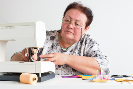 pastime: patchwork and quilting at the workshop of a tailor woman on white background - older woman with glasses is preparing to work on the sewing machine with scraps of colored fabrics Stock Photo