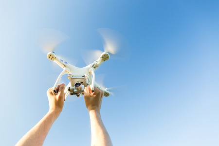 quadcopter outdoors, aerial imagery and recreation concept - closeup on human hands grip on frame of white quadrocopter flying on background of blue cloudless sky, male man caught flying drone Stock Photo