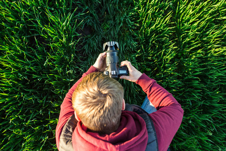 pastime: fascinating photography and process of shooting concept - top view of young male man with mirror camera in hands standing in a field of bright green grass, jeans and jacket hoodie