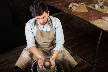 fireclay: potter, workshop, ceramics art concept - young man working on potters wheel with raw fireclay with hands, a male sculpts a utensil near wooden table with tools, master in apron and shirt, top view