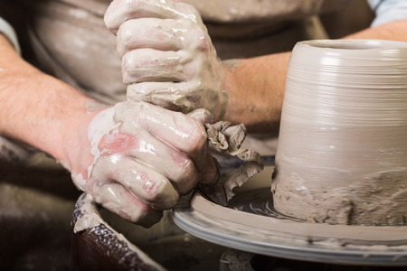 pastime: pottery, workshop, ceramics art concept - male hands work with potters wheel, fingers form shape of raw clay, male master sculpt a utensil with carving tool, front view