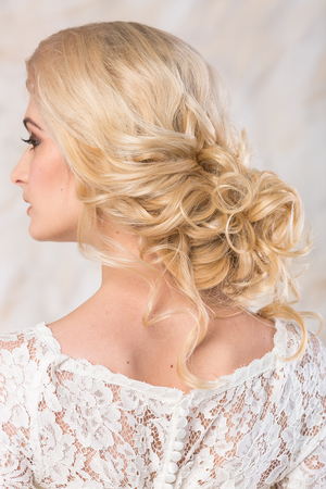 white sleeve: fashionable gown, beautiful blonde model, bride hairstyle and makeup concept - back view on young charming lady in wedding white dress standing indoors on light background, pretty woman posing Stock Photo