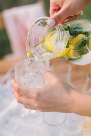 picnic, food, summer, holiday concept - female hands pouring lemonade from the decanter into a glass tumbler, glass pitcher with slices of lemon, lime, water, mint leaves, selective focus