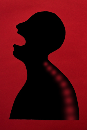 concept of human disease and pain localization on silhouette - abstract african man with sharp pain in the spine, open mouth, isolated on red background, top view, flat lay Foto de archivo