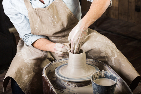 pottery, workshop tools, ceramics art concept - man hands work with potters wheel, the fingers form the shape of raw fire clay, young male sculpt a utensils with a sponge, master in apron, top view Stock Photo