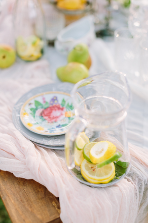 lifestyle, decoration, healthlife, country concept - still-life with jug full of sliced lemon and mint and plates with flower print on light pink draping Stock Photo