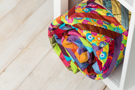 patchwork, sewing and fashion concept - beautiful colorful quilted blanket at white shelves in studio, background of white floor in a warehouse, finished stitched coverlet, top view