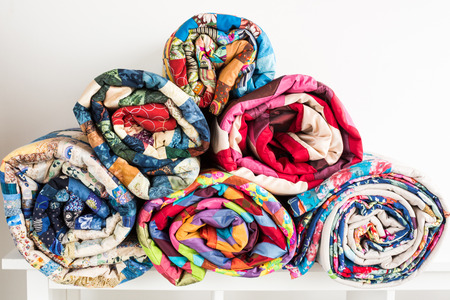 counterpane: patchwork, sewing and fashion concept - bright beautiful quilts stacked in several rows in height for the storage, sale of finished stitched coverlets on white background, front view