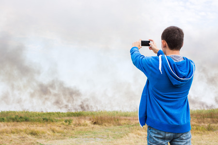 documenting: the man filming strong smoke over the burning fields of ripe wheet during the strong heat and a drought in the summer. Stock Photo