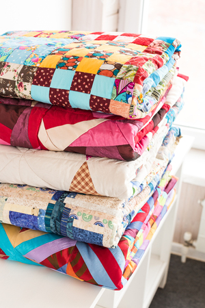 patchwork and fashion concept - beautiful stack of colorful quilts, bedspreads stacked in several rows in height for storage, sale of stitched products on a white background Фото со стока