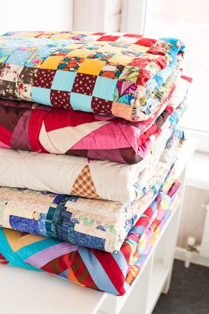 patchwork en mode concept - mooie stapel kleurrijke dekbedden, spreien gestapeld in verschillende rijen in de hoogte voor opslag, verkoop van gestikte producten op een witte achtergrond