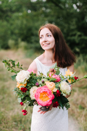 beauty, wedding, spring, nature, decoration concept - shapely smiling woman with dark brown hair in white party dress with colorful bouquet composed of beautiful peonies, roses and carnations