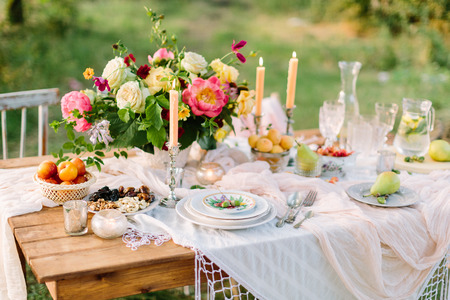 womens day, wedding, celebration, romance, picnic, nature concept - gorgeous table setting with snow white tablecloth, dishes, clear wine-glasses, silver candleholders and various fruits