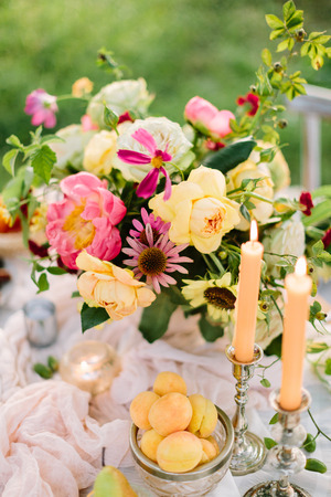 weekend, feeding, nature concept - romantic table setting with delicate yellow apricots, silver candleholders and great bunch of roses, bright pink peonies, marsala colored carnations and dianthuses
