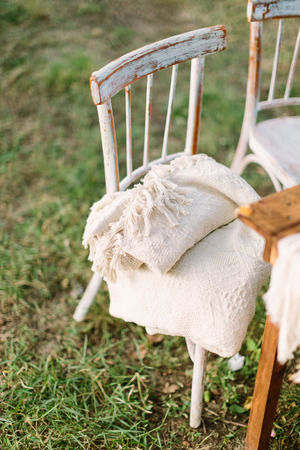 picnic, furniture, decor concept - vintage wooden antique chairs with rugs lying at the summer picnic near a wooden table on natural grass Stock Photo