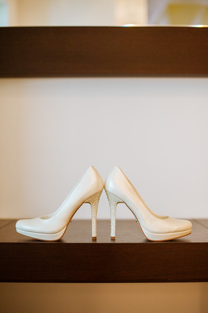 gatherings of the bride on a wedding. elegant beige wedding shoes with high heels in a white interior. brides accessories. Imagens - 81672138