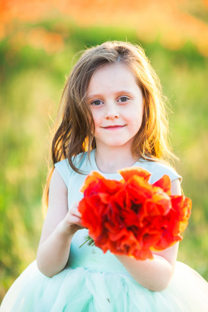feast: wedding, childhood, flora concept - portrait of beautiful girl of preschool age with sly smile and flowing light brown hair, shes wearing alice blue dress and holding bright bouquet of poppies Stock Photo