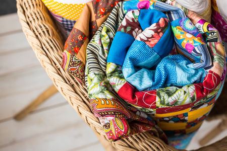 patchwork and fashion concept - macro on beautiful quilts rolled into a tube and laid in a wicker chair, warehousing of finished stitched products on a white background, top view, flat lay