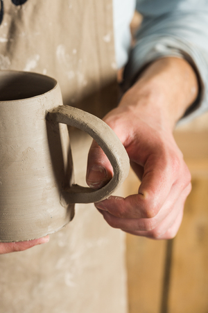 pottery, workshop, ceramics art concept - ceramist holding unfinished clay cup and carefully examines the product, male master dressed in a stained clay apron, craftsman's hands holding unbaked jug