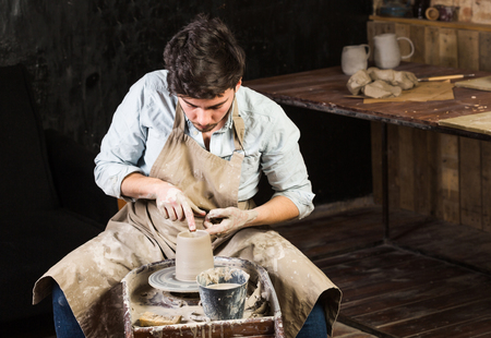pottery, workshop, ceramics art concept - young male master works with hands and potter wheel, brunette male fingers sculpt some new jug from raw clay with water, close-up Reklamní fotografie - 82242475