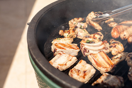roasting pan: food, picnic, recipes and meat concept - closeup on a delicious cooking pork ribs grill pan along with the sausages, turning pieces for even roasting by metal kitchen tongs, sunny festive day on lawn