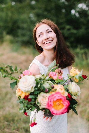 bouquet, people and floral arrangement concept - young smiling woman with brown hair and colourful bouquet in hands, pink peonies, roses, carnations, happy female in white dress on background of trees