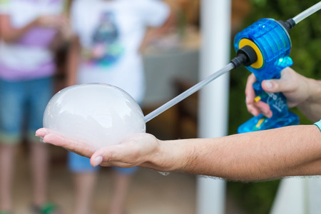 handheld device: magic show performance, holiday celebration and miracle concept - male illusionist inflates bubble with smoke gun on a palm, soap bubbles concert, compact fog machine, selective focus