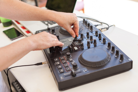 crossfader: music technology, holiday party concept - male hands of Dj mixes audio track, beautiful black hi end disc jockey mixing device, digital concert equipment, resort entertainments, selective focus