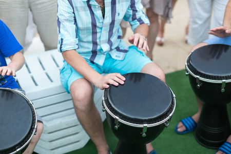drum, percussion instruments and culture concept - closeup on hands of musicians playing withl turkish darbuka, summer outdoors concert performance, ethnic rhythm performance, selective focus Stock Photo