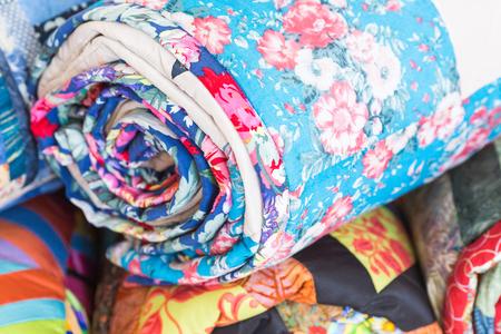 Zelfgemaakte, kledingindustrie, ambachtelijke concept. Macro op een perfect genaaid deel van de beddeksel voor het bed met afbeeldingen van gewichtloze roze anjers gedraaid in rol