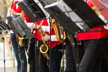 clarinete: brass band, musical instrument, orchestra concept - festive performance of saxophones and clarinet, closeup on sheet music stands and sax, musicians in red concert jackets, selective focus Foto de archivo