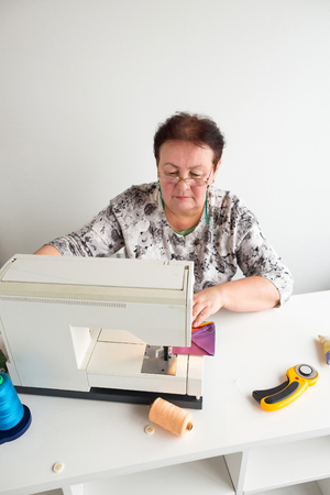 sewing machines: patchwork and quilting workshop of a tailor woman - older woman with glasses works at a desk with a sewing machine and thread, fabrics, needles, pins, buttons, rotary fabric cutters