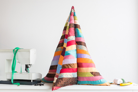 quilting - high pillow in the form of a pyramid of colorful quilted fabrics made of pieces of patchwork fabrics on the table next to the scissors, scraps of fabrics, coils of thread, sewing machine