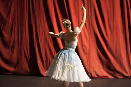 backstage, practice, culture concept. red curtains of theater are still closed and slim ballerina dressed in costume for perfomance with poofy sleeves and flowers in her hair rehearsing her part Stock Photo