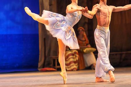 ballet, liefde, theaterconcept. dansduet van twee personen, ballerina-achtig porseleinen beeldje dat op een uitgerekte teen staat en vasthoudt aan haar stoere mannelijke partner
