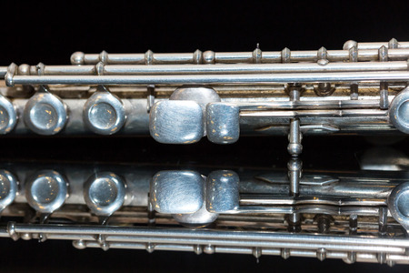 flute key: symphonic music concept - closeup on western concert flute lies on the pure black mirror surface, middle body section of instrument with majority of keys, marching, orchestra concerts, macro