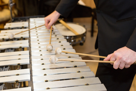 closeup on wooden bars with four mallets in human hands, performer in black dress, glockenspiel, art of music, selective focus