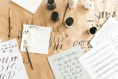 calligraphy, design, creativity concept. workspace preparing for practice in calligraphy with all requisite equipment such as ink of two color blac and white, brushes, lots of paper and few napkins Standard-Bild
