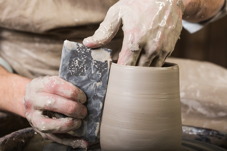 fireclay: pottery, workshop, ceramics art concept - closeup on male fingers sculpt new utensil with a tools and water, mans hands working with potters wheel and raw fire clay, close view