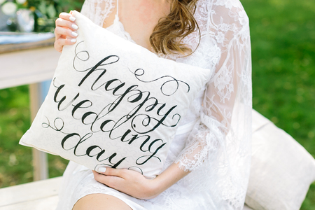 velvet dress: comfort, holiday, celebration concept. young fair-haired woman wearing radiant lace cloak on her shoulders keeping small cushion with words printed in italic style